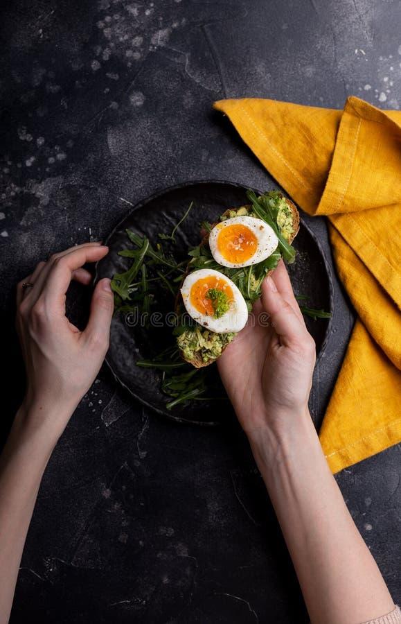 Sandwich mit Ei und Avocado auf Brot in den H?nden der Frau lizenzfreie stockbilder