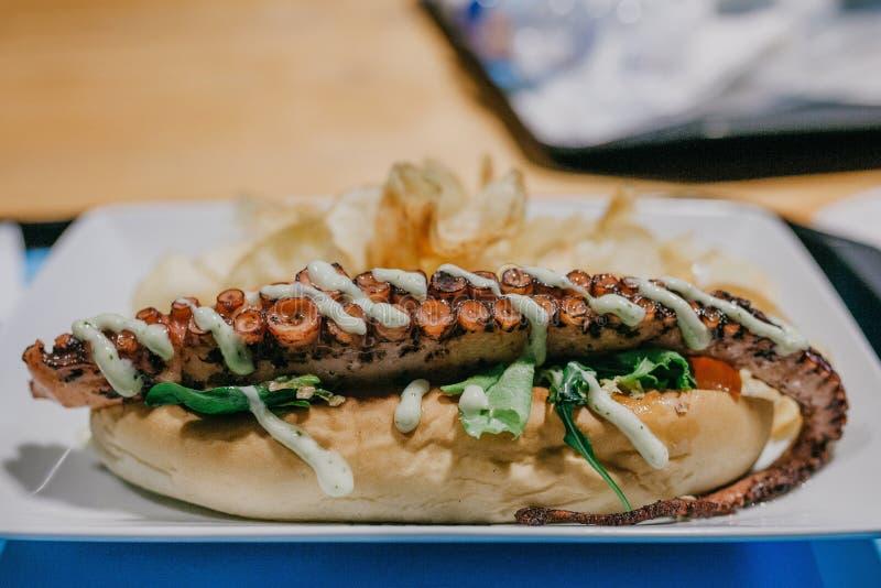 Sandwich mit einer Krakententakel Gebratene Fische mit Petersilie auf einer Platte lizenzfreie stockfotografie