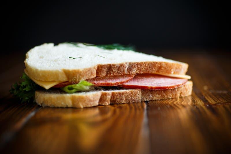 Sandwich mit frischem Salat und Grüns und Wurst lizenzfreies stockbild