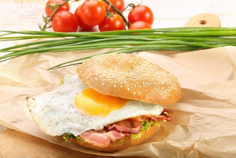 Sandwich mit gebratenem Speck und Ei auf einem hackenden Brett stockbild
