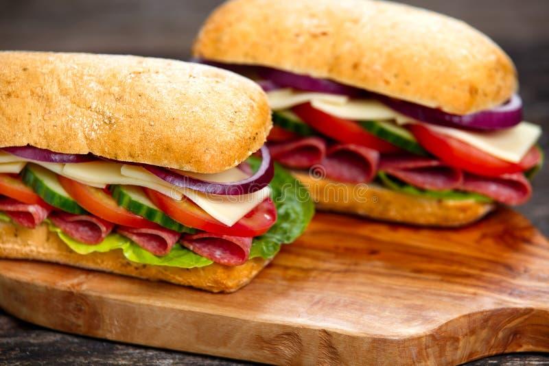 Sandwich mit Kopfsalat, Scheiben von frischen Tomaten, Gurke, rote Zwiebel, Salami und Käse stockfotos