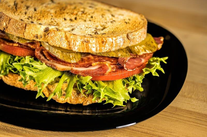 Sandwich mit Kopfsalat, Schinken, Tomaten und in Essig eingelegten Gurken Sandwich liegt in einem Schwarzblech auf einem Holztisc stockbilder