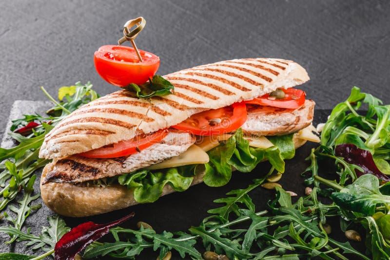 Sandwich mit Leiste gegrilltem Huhn, Frischgem?se, K?se und Gr?ns auf Brett des schwarzen Schiefers ?ber schwarzem Steinhintergru lizenzfreie stockfotos