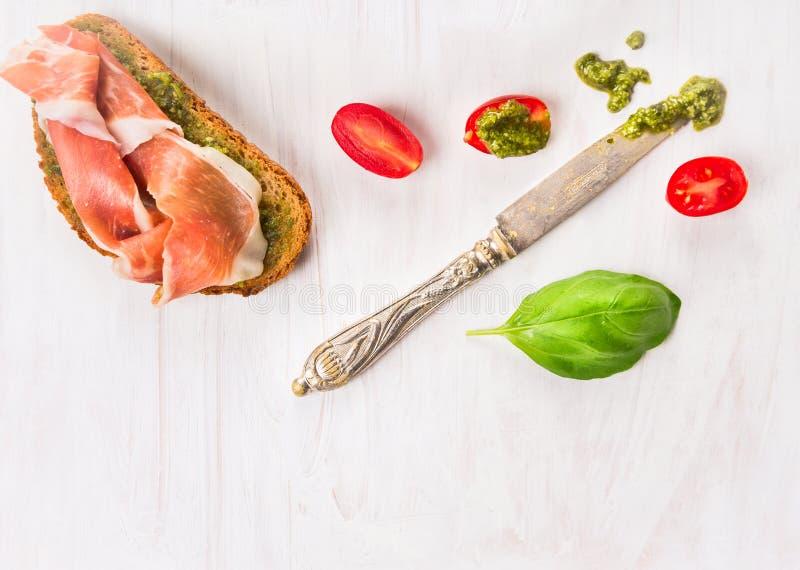 Sandwich mit Parmaschinken, Basilikum Pesto, Tomaten und Messer lizenzfreie stockbilder