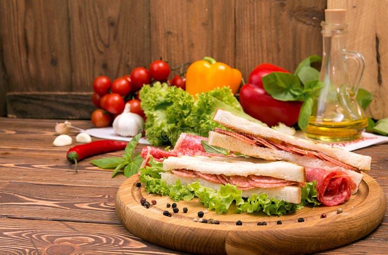 Sandwich mit Salami Kopfsalat, Kirschtomaten, Senf, Basilikum, stockfotografie