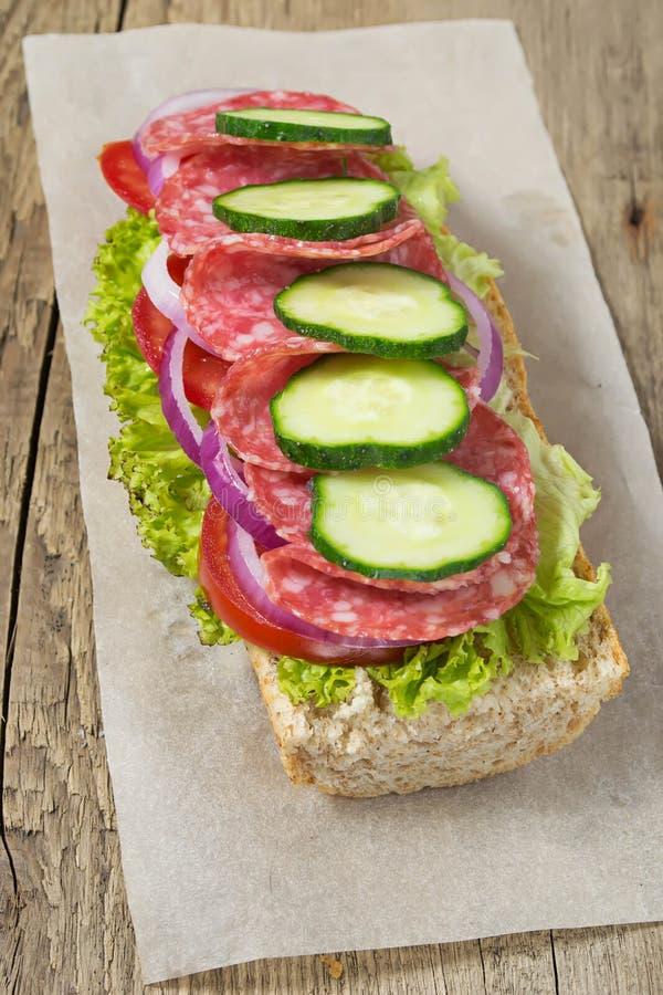 Sandwich mit Salami, Tomate und Kopfsalat lizenzfreies stockbild