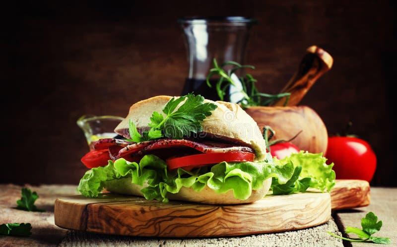 Sandwich mit Schinken, Kopfsalat und Tomate im Weizenbrötchen, Weinleseholz stockfoto