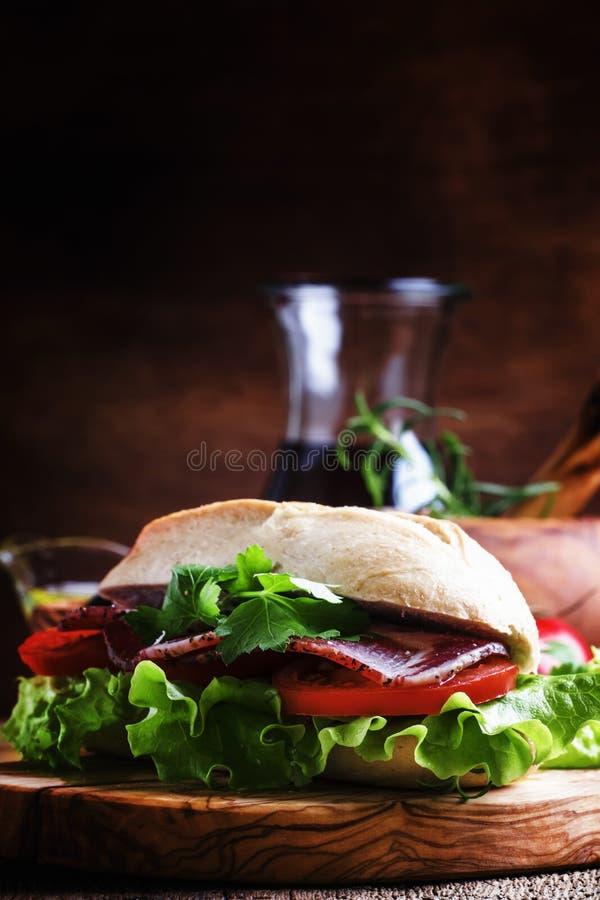 Sandwich mit Schinken, Kopfsalat und Tomate im Weizenbrötchen, Weinleseholz lizenzfreie stockfotos