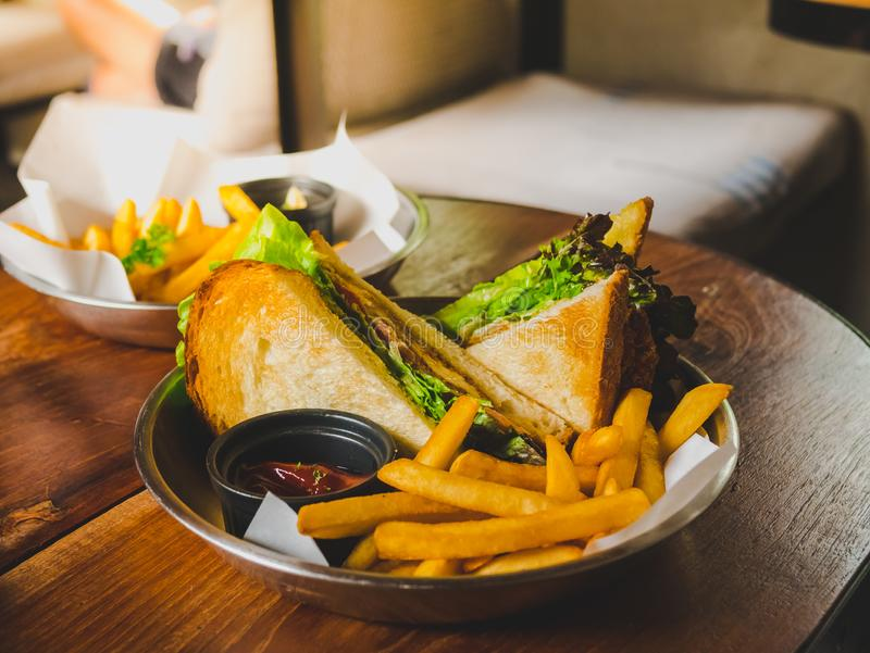 Sandwich mit Thunfischgemüse, Tomate, Käse und goldenen Pommesfrites auf Holztisch stockfotos