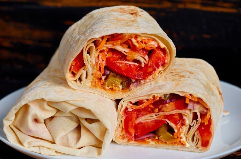 Sandwich ou lavash à Shawarma avec les légumes frais et la sauce du plat blanc sur le fond en bois foncé de cuisine photo libre de droits