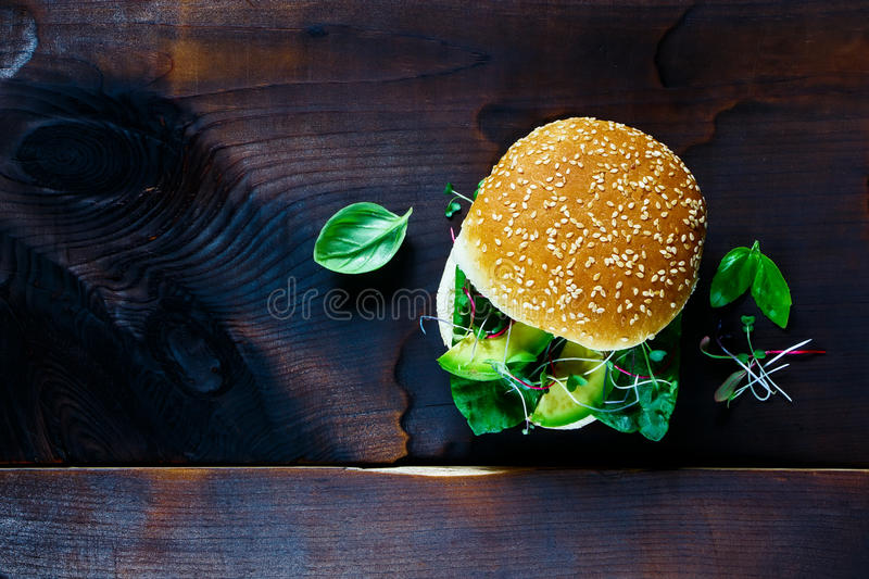 Sandwich over old wood. Avocado, spinach, basil and sprout sandwich over old wood dark background, top view, copy space royalty free stock photo
