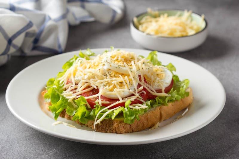 Sandwich ? pain blanc avec de la laitue, la tomate, l'oeuf ? la coque et le fromage r?p? D?jeuner d?licieux, petit d?jeuner sain  photographie stock