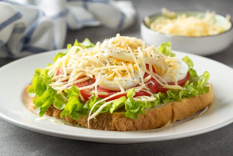 Sandwich ? pain blanc avec de la laitue, la tomate, l'oeuf ? la coque et le fromage r?p? D?jeuner d?licieux, petit d?jeuner sain  image libre de droits