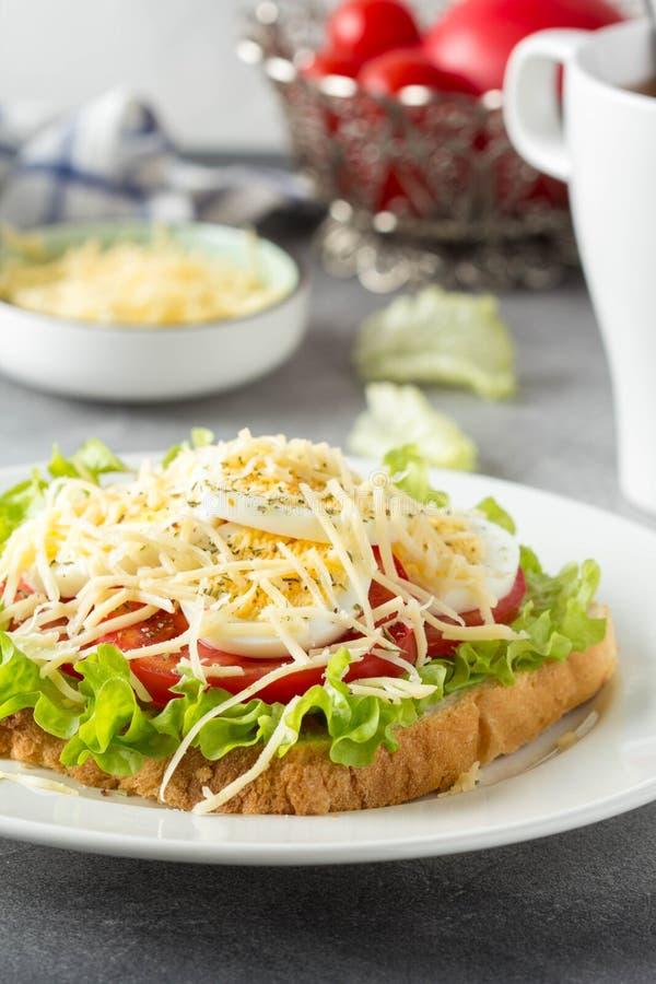 Sandwich ? pain blanc avec de la laitue, la tomate, l'oeuf ? la coque et le fromage r?p? D?jeuner d?licieux, petit d?jeuner sain  photo libre de droits