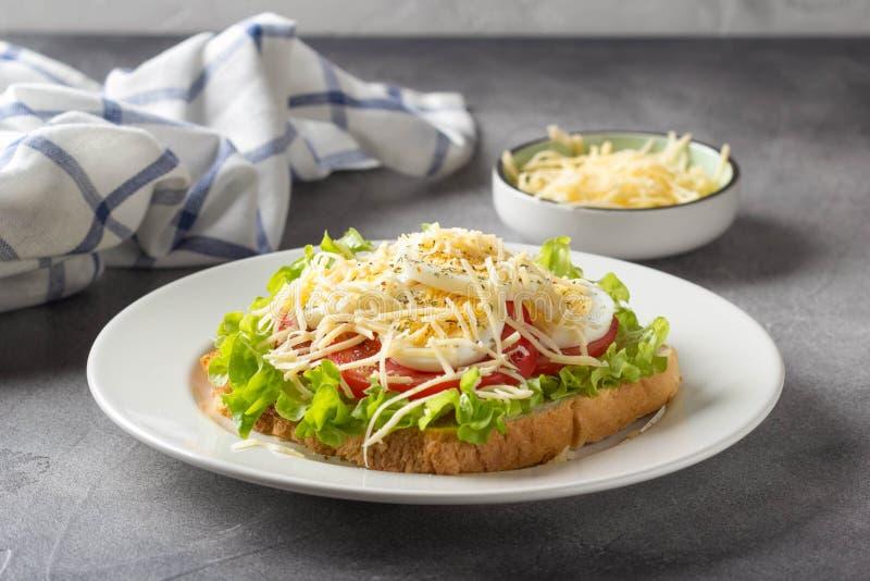 Sandwich ? pain blanc avec de la laitue, la tomate, l'oeuf ? la coque et le fromage r?p? D?jeuner d?licieux, petit d?jeuner sain  images stock
