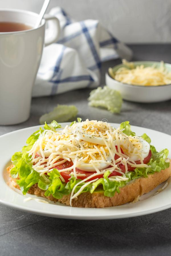 Sandwich ? pain blanc avec de la laitue, la tomate, l'oeuf ? la coque et le fromage r?p? D?jeuner d?licieux, petit d?jeuner sain  photographie stock libre de droits
