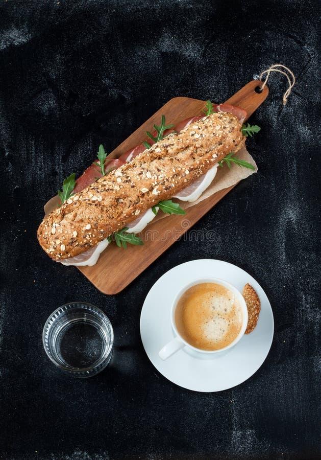 Sandwich (prosciutto, arugula), koffie en water stock foto