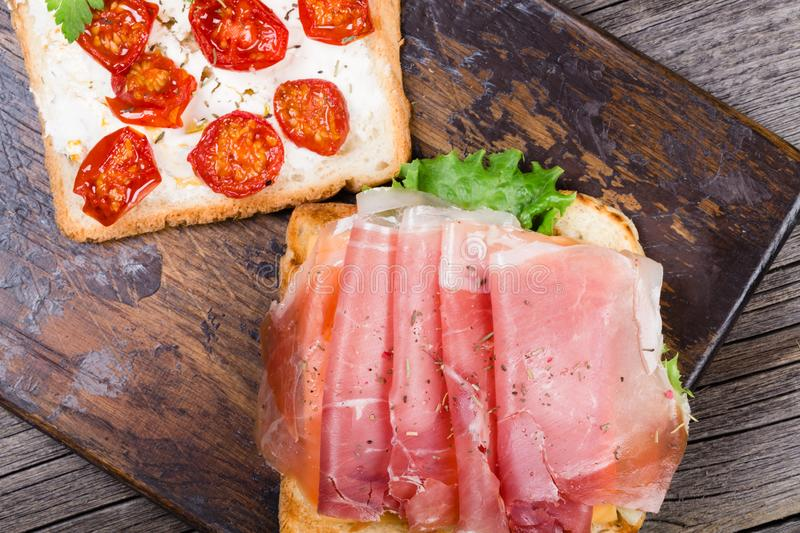 Sandwich with prosciutto and dried tomato stock images