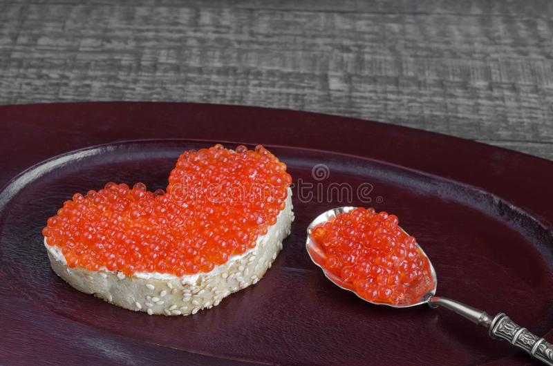 Sandwich with red caviar in the form of heart on a wooden tray. Analog products. Sandwich with red caviar in a heart shape and spoon on wooden tray and grey royalty free stock photo
