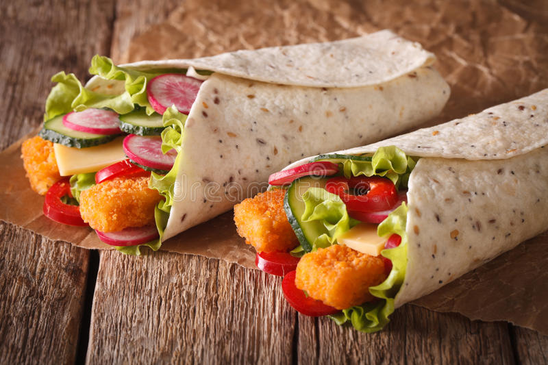 Sandwich roll with fishfingers, cheese and vegetables close-up. royalty free stock photography