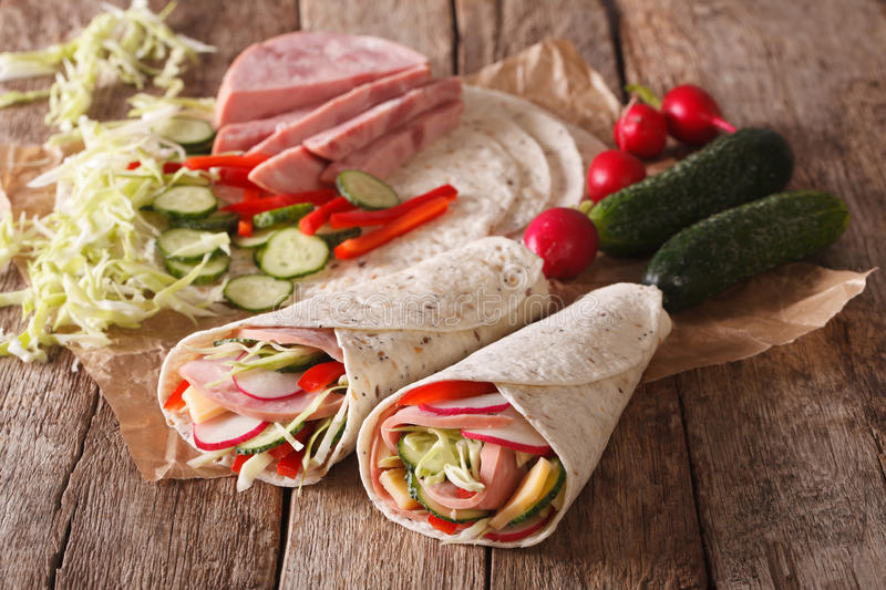 Sandwich rolls with ham, cheese and vegetables close-up and ingredients. horizontal royalty free stock photo