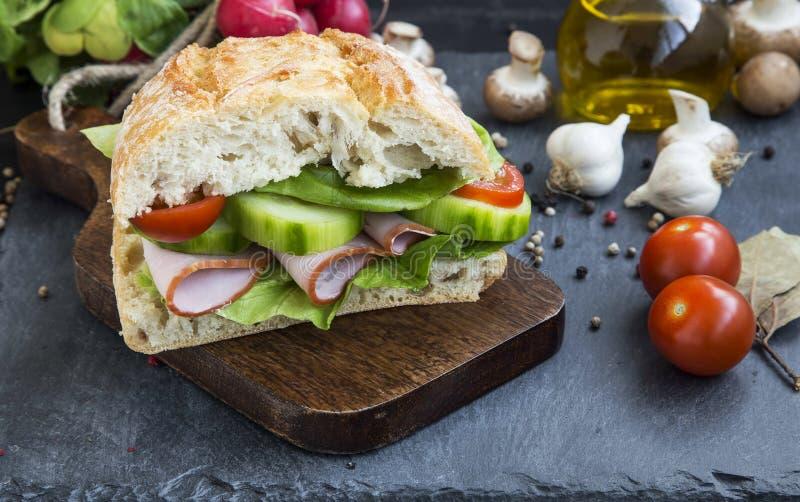 Sandwich rustique avec du jambon, le pain frais, la salade, les tomates et le concombre photographie stock libre de droits