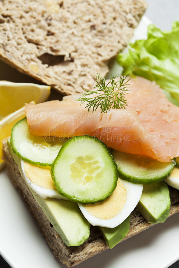Sandwich. Rye bread sandwich with avocado, eggs, cucumber and smoked salmon stock image