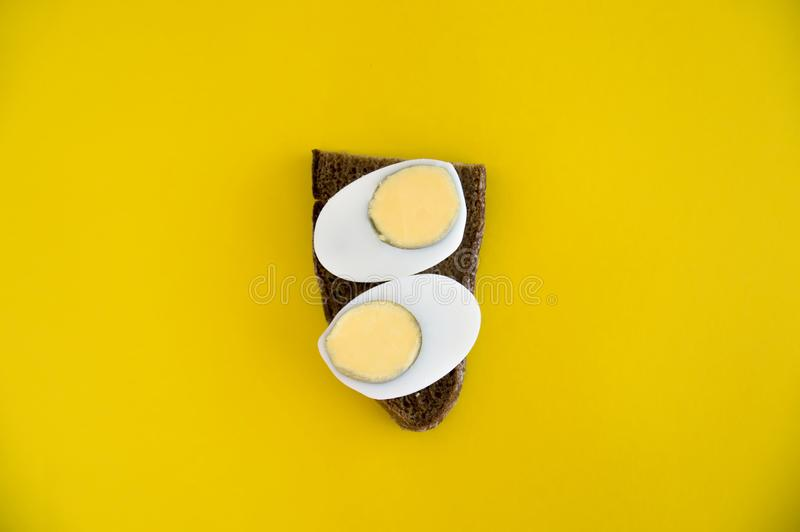 A sandwich of rye bread and boiled egg lies on a yellow background. Breakfast for diet. Toast with bread and egg dietary breakfast royalty free stock photo