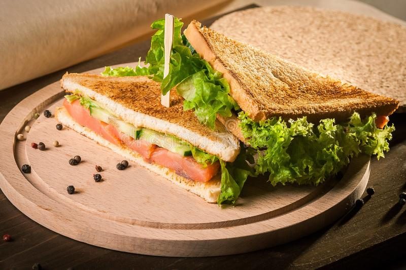 Sandwich with rye brown bread, frash satad and red fish on wooden board royalty free stock photo