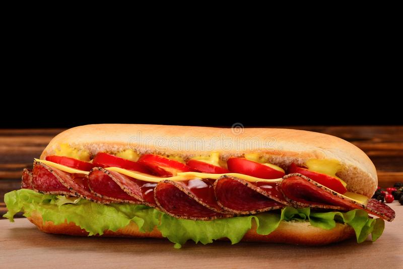 Sandwich with salami, cheese, cherry tomatoes, lettuce and mustard on a black background. Space for text or design. royalty free stock photos