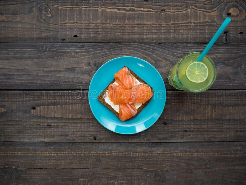 Sandwich with salmon, avocado, black bread on a plate and a glass of lemonade stock photos