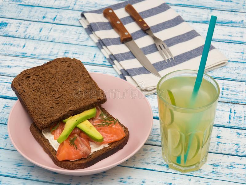 Sandwich with salmon, avocado, black bread on a plate and a glass of lemonade royalty free stock images