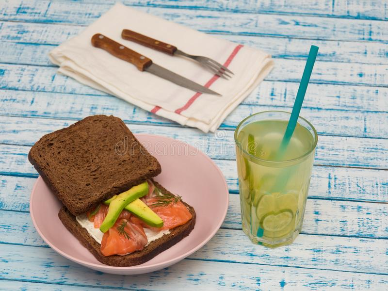 Sandwich with salmon, avocado, black bread on a plate and a glass of lemonade stock image