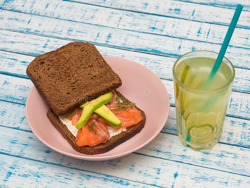 Sandwich with salmon, avocado, black bread on a plate and a glass of lemonade stock images