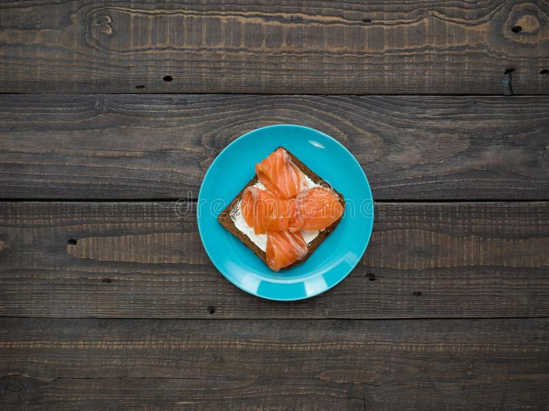 Sandwich with salmon, avocado and black bread on a plate stock images