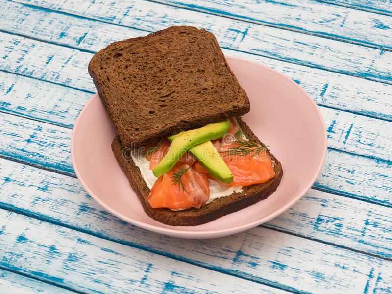 Sandwich with salmon, avocado and black bread on a plate stock photography