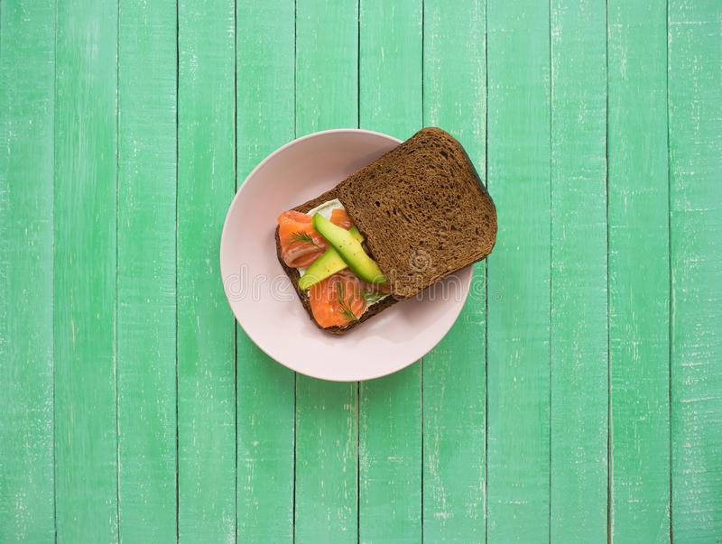 Sandwich with salmon, avocado and black bread on a plate royalty free stock images