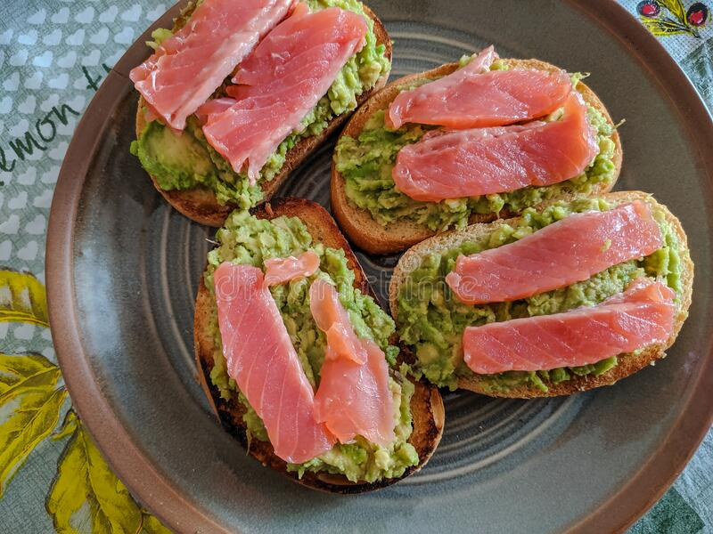 Sandwich with salmon and avocado on a plate, top view. Healthy eating concept stock photography
