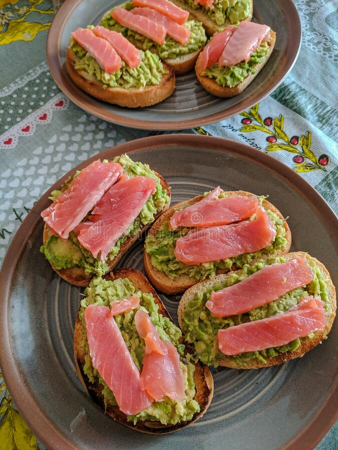 Sandwich with salmon and avocado on a plate, top view. Healthy eating concept stock image