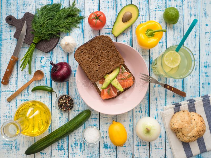 Sandwich with salmon, black bread on a plate, vegetables and a glass of lemonade stock image