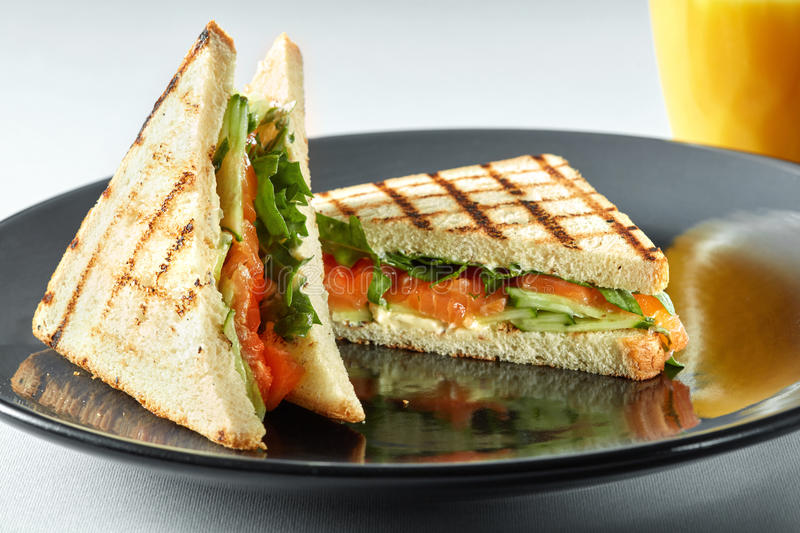 Sandwich with salmon and orange juice for breakfast royalty free stock image