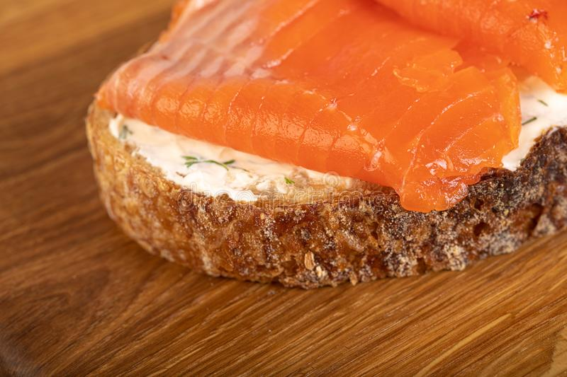 Salmom sandwich. Sandwich with salmon on wooden board stock image