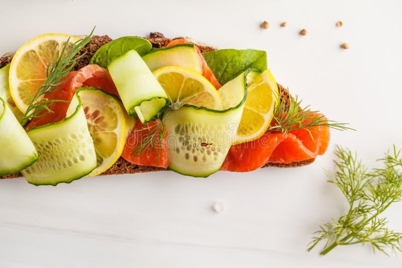 Sandwich saumoné coupé en tranches à poissons de truite avec les ogerets, le pain de seigle et photographie stock