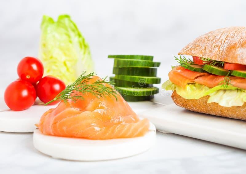 Sandwich saumoné sain frais avec de la laitue et concombre et tomates sur le conseil de marbre sur le fond de marbre blanc Casse- photographie stock