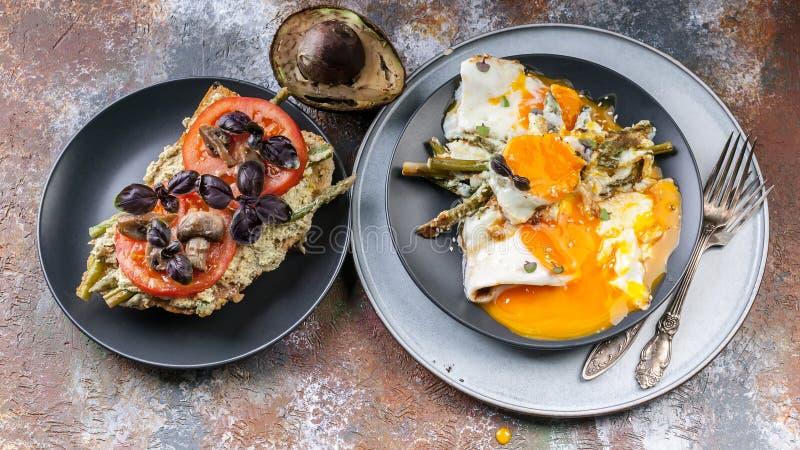 Sandwich savoureux à petit déjeuner avec des tomates et des champignons, basilic, avocat, oeufs au plat avec l'asperge Vue sup?ri photographie stock libre de droits