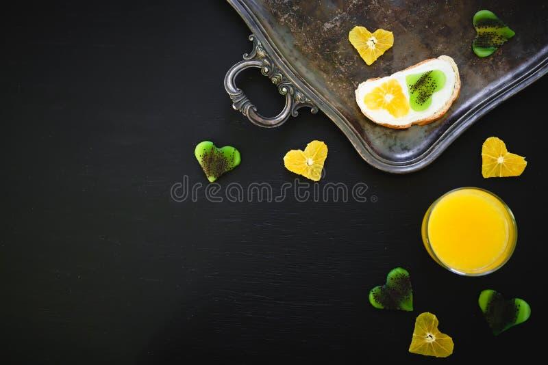 Sandwich savoureux avec les fruits et le jus d'agrumes frais sur le fond noir Configuration plate, vue supérieure photo stock