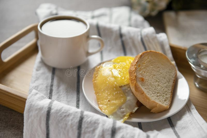 Sandwich with scrambled eggs and cheese on wheat bread,  Cup of black coffee on a tray royalty free stock images