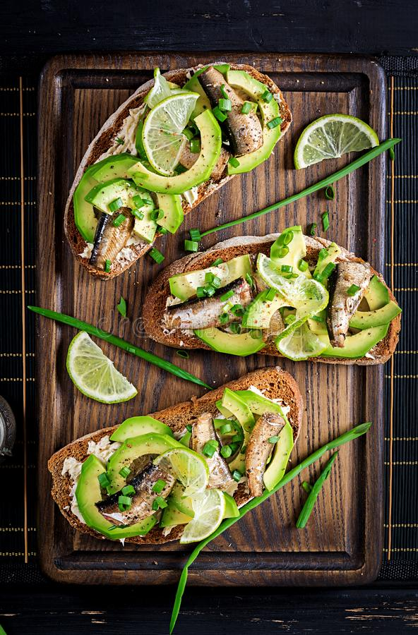 Sandwich - smorrebrod with sprats, avocado and cream cheese on wooden board. stock photos