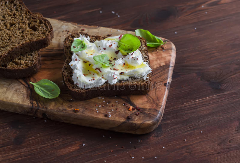 Sandwich with soft cheese, olive oil and basil, served on olive cutting board on dark wooden surface. royalty free stock images