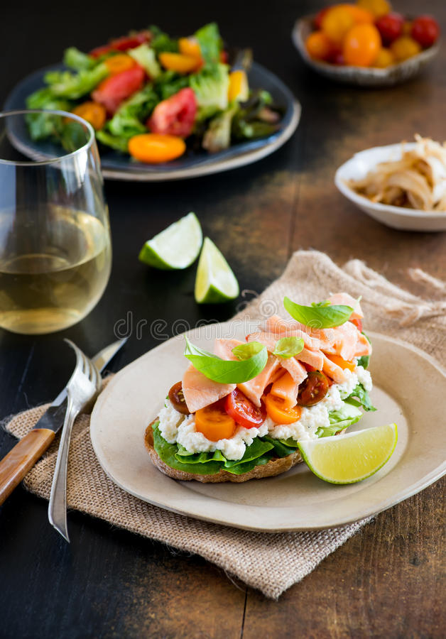 Sandwich with sogt cheese, salmon and tomatos. Sandwich with soft cheese, salmon and tomatos on plate over rustic wooden background, white wine and fresh salad stock photos